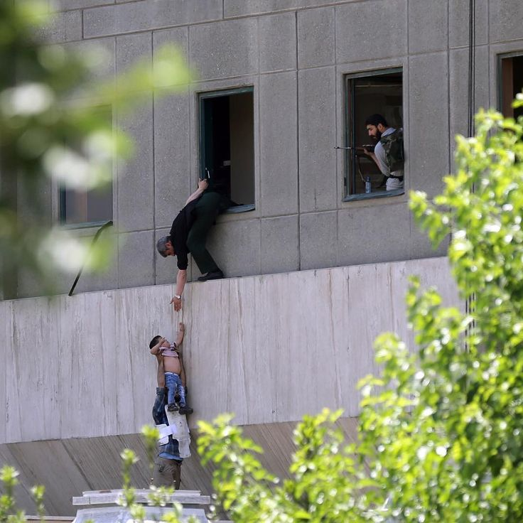 Suicide bombers and gunmen stormed into Iran's parliament and targeted the shrine of Ayatollah Ruhollah Khomeini, killing 12 security guards and wounding 42 others in rare twin attacks. In this photograph, policemen try to help civilians fleeing from the parliament building during the attack in Tehran, Iran, June 7, 2017.  Read more on TIME.com.  Photograph by Omid Wahabzadeh—EPA.  #iran