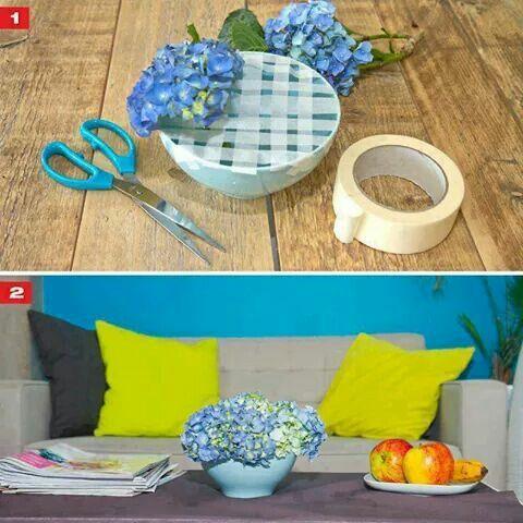 Creativa idea de hacer un arreglo floral en un tazón o bowl. Usa cinta adhesiva o masking tape para cubrir en forma de cuadrícula la abertura del bowl, luego en cada rendija coloca las flores, ramas u hojas. No olvides colocar agua antes.