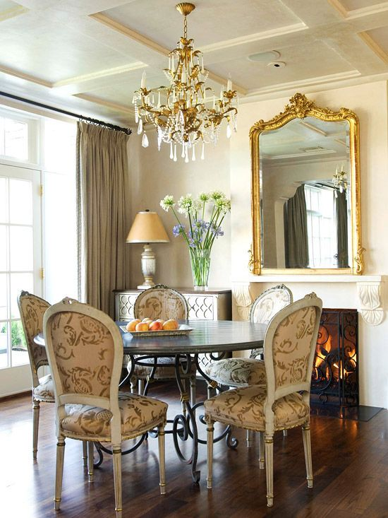 Gather Round A round dining table allows for easy conversation flow. Armless chairs maximize the seating capacity at this table, while peekaboo fabric backs ensure an eye-pleasing view from every vantage point. A gilded chandelier and a mirror above the mantel reflect the golden imprints found on the chairs.