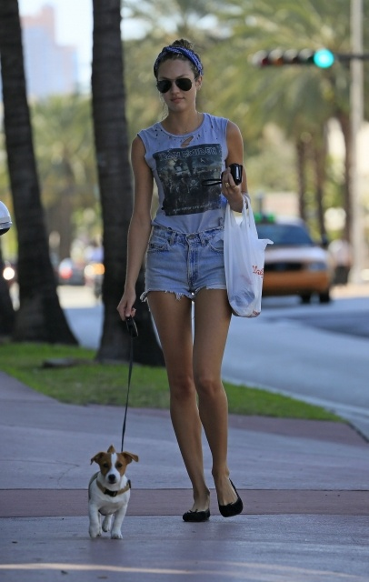 Candice Swanepoel walks her dog on the way to buying groceries at Walgreens wearing a bandana and an Iron Maiden tee-shirt in South Beach, Florida.