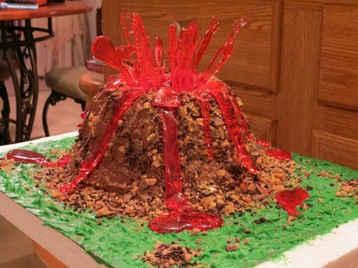 Edible Volcano Cake-Triple chocolate fudge cake with whipped milk chocolate frosting, chocolate sprinkles, milk chocolate toffee bits, red-colored hard candy lava, & green icing as surrounding grass.