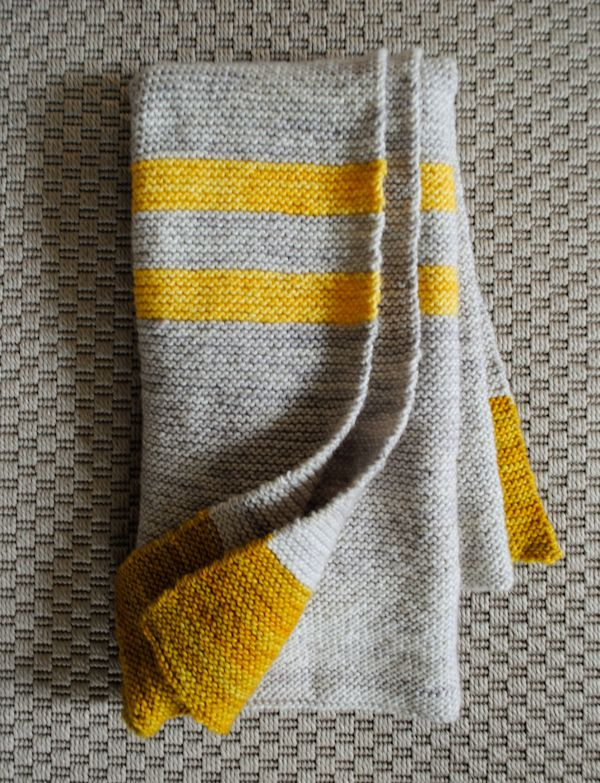 This baby blanket is for the parents who are not afraid to branch away from conventional pastel blues and pinks when it comes to their little one. The pop of yellow against grey in this color blocked design is a little different and very modern.