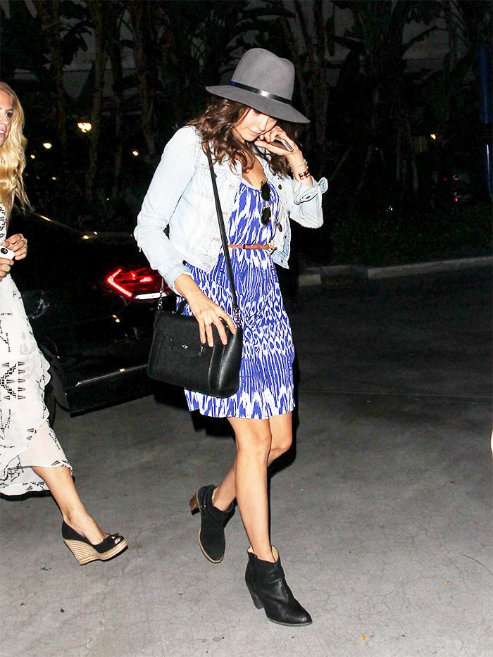 Nina Dobrev wears a printed blue and white dress with a denim jacket, black leather boots, a black crossbody bag, and a grey fedora