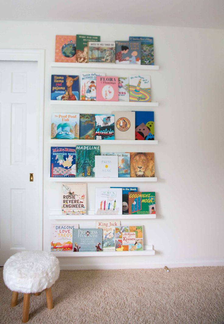 Here is a great budget-friendly small-space solution for displaying children's books, plus it's so colorful it looks like a piece of artwork! This is a wonderful visual and practical element for any nursery with an empty wall. For this and other budget-friendly DIYs make sure to check out All Things Big And Small--a blog where stylish motherhood and budget-friendly DIYs meet!