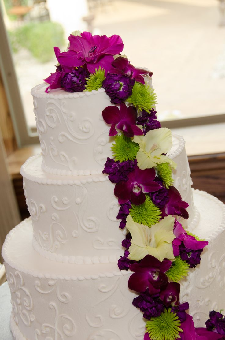 Wedding cake accented with purple and green flowers. I love the colors!!