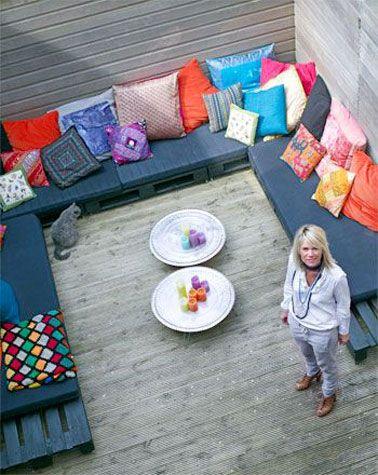 Un grand canapé en U sous de palettes de bois sur la terrasse, pour de bons moments conviviaux à partager.