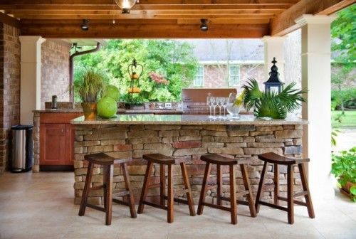 I love the idea of an outdoor kitchen/living space. So where do I begin with this pic?! I so L O V E the stone bar! Love the stools. Love the contrast of the wood cabinets & beams w/ the stone & bricks. Love the floor...love this! : )