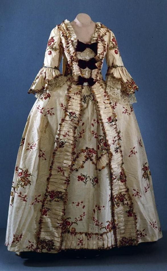 Dandridge Robe à la française: ca. 1750 (textile), ca. 1770 (gown remodeled), American, Spitalfields (silk), silk lustring  with brocaded floral bouquet entwined with weft-float pattern of trailing vine and flowers, open front style (with matching petticoat), flounced and lined sleeves, trimmings padded with cotton, embellished with colored silk fly-fringe. [Search for Acc. No. 1975-340,1]