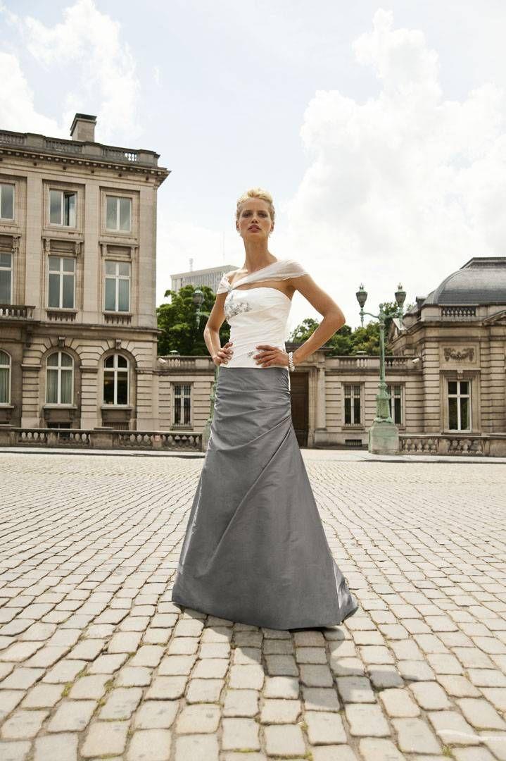 Prachtige 2-delige bruidsjurk in off white & zilver grijs. De zilveren bloem accenten op de top zorgen voor de perfect match. De gedrapeerde tule om de schouders geeft deze outfit net dat tikje extra.
