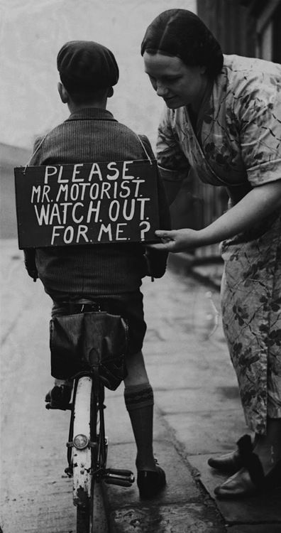 A mother fastening a notice reading 'Please Mr Motorist, watch out for me', onto her son's back before he sets out on a trial bicycle ride, 1937.
