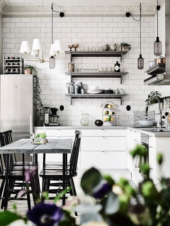 Modern vintage kitchen with white cabinets and back splash and grey wooden accents and table