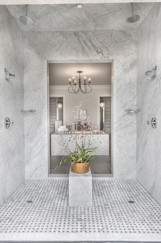This multi-person marble shower hosts a sitting bench and several shower heads. Photo: Paul Rollins Photography