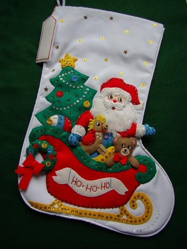 """This wonderful Christmas Stocking called """"SANTA'S SLEIGH"""" is made of felt applique on cloth and beautifully decorated with hand sewn sequins and beads. Portions of this stocking are stuffed creating a three dimensional appearance. Many hours of work went into completing this adorable stocking, perfect for any little boys or girl. This measures approx. 21"""" diagonally and 10"""" across the top...hanging name tag is included."""
