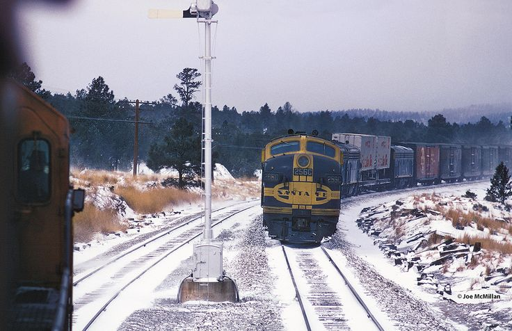 https://flic.kr/p/CGcDbE | Cold Meet | You are riding the second unit of Train #23 entering the siding at Fox, New Mexico, to meet the Extra 256C East. This very chilly scene was photographed 47 years ago on December 21, 1968. No. 23 is already late and will be almost a day late by the time it reaches Los Angeles. Note the odd placement of the TOFC behind the engine consist and ahead of a deadheading F7B. Photo by Joe McMillan.