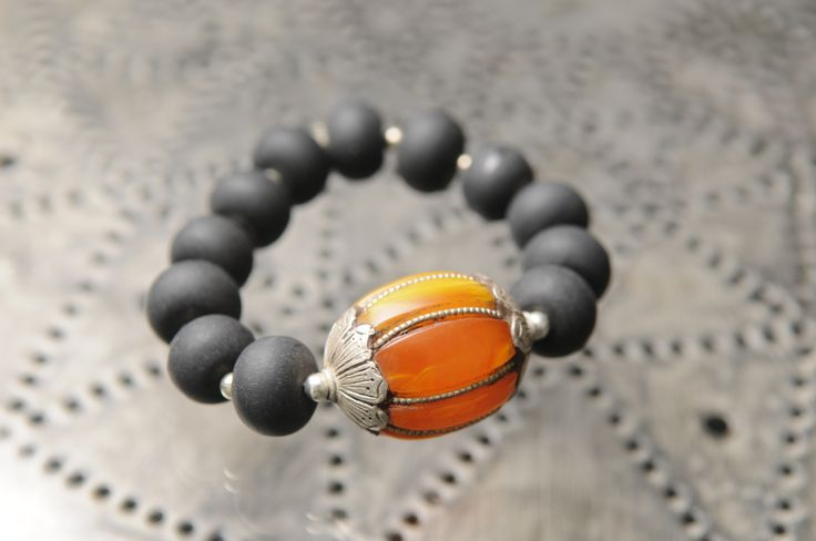 Tinky bracelet made with black resin beads and a single Tibetan amber feature bead. https://www.facebook.com/TinkySonntag
