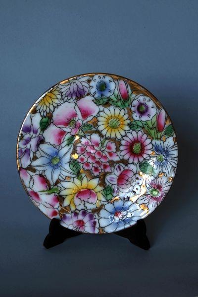 Bonito platito de cerámica Macao. Protagonista de su decoración coloridas flores enmarcadas por el brillo del dorado. Llamativa y alegre composición.