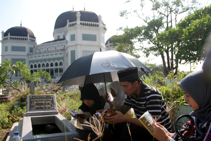 A family prays near the tomb of their relative at the Al-Mashun Grand Mosque cemetery in Medan on Sunday. Indonesian Muslims visit the graves of their relatives ahead of the Islamic fasting month of Ramadhan. (Antara Photo/Irsan Mulyadi)