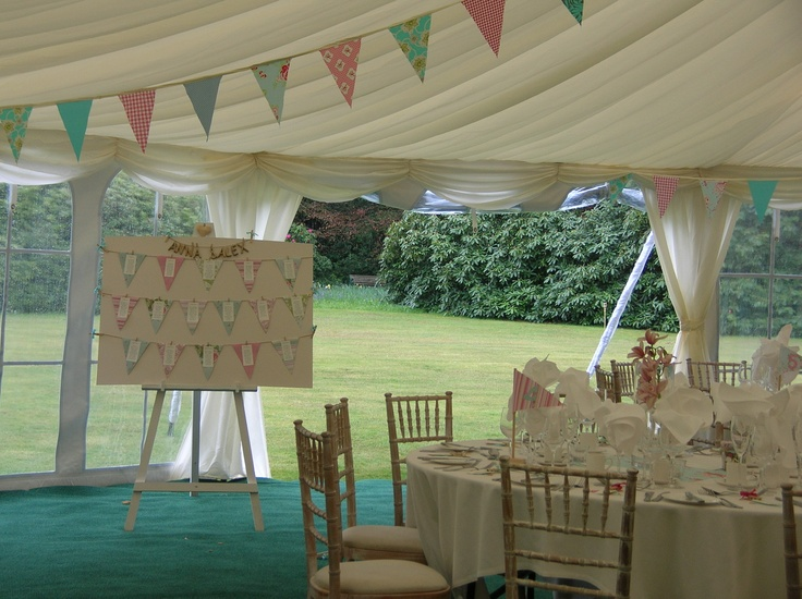 A pretty marquee with windows rolled up allowing guests to spill out onto the gorgeous lawns of Hollybank House a beautiful wedding venue in Emsworth, Hampshire.  Marquee supplied by Southern Marquees Ltd.