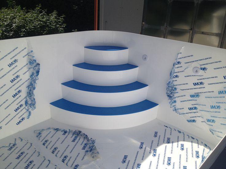 Bílý bazén s rohovýma schodama, které mají modré nášlapy