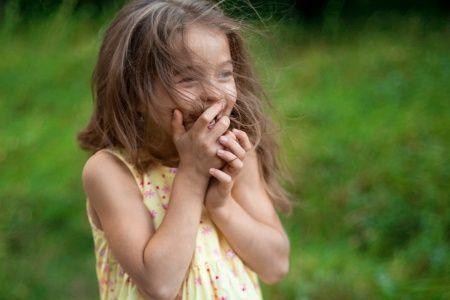 Маленькая девочка смеется