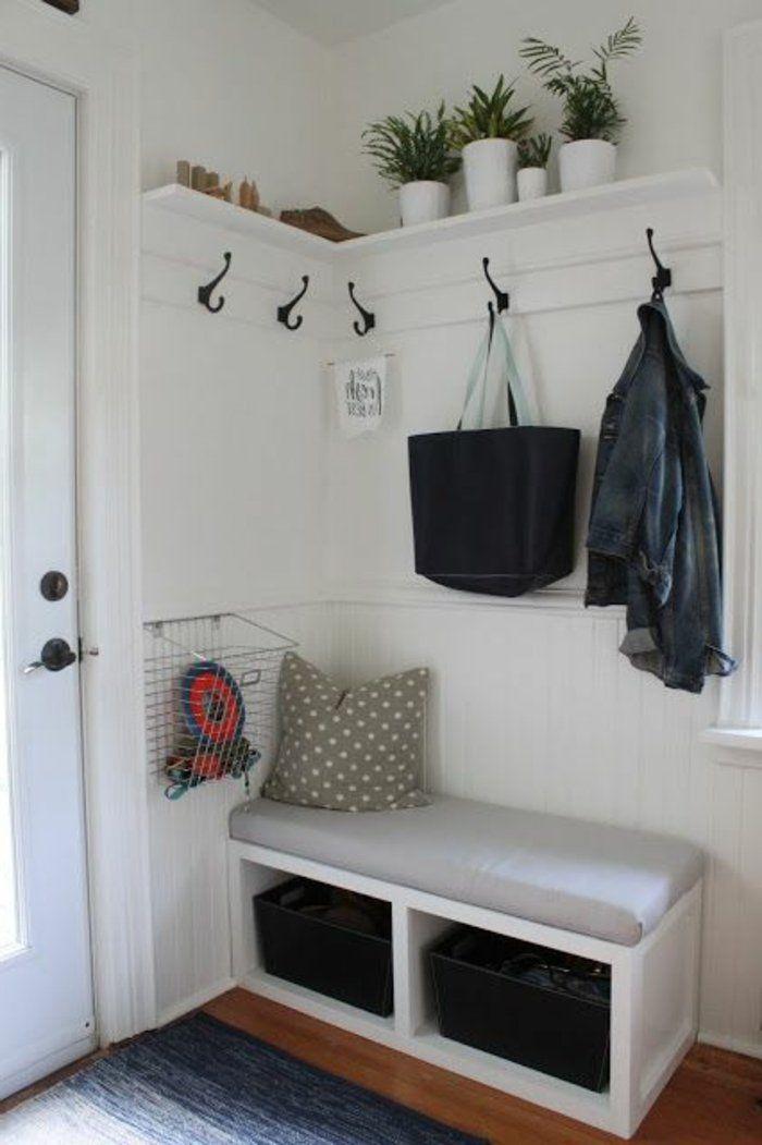 Décorer un couloir. Des pots de plantes vertes sont poses près du plancher. Un sac noir est pendu.