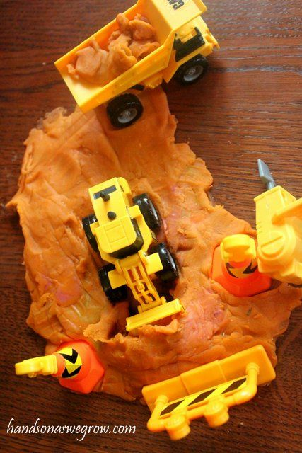 Add construction vehicles to play dough for a busy play construction site for the kids!