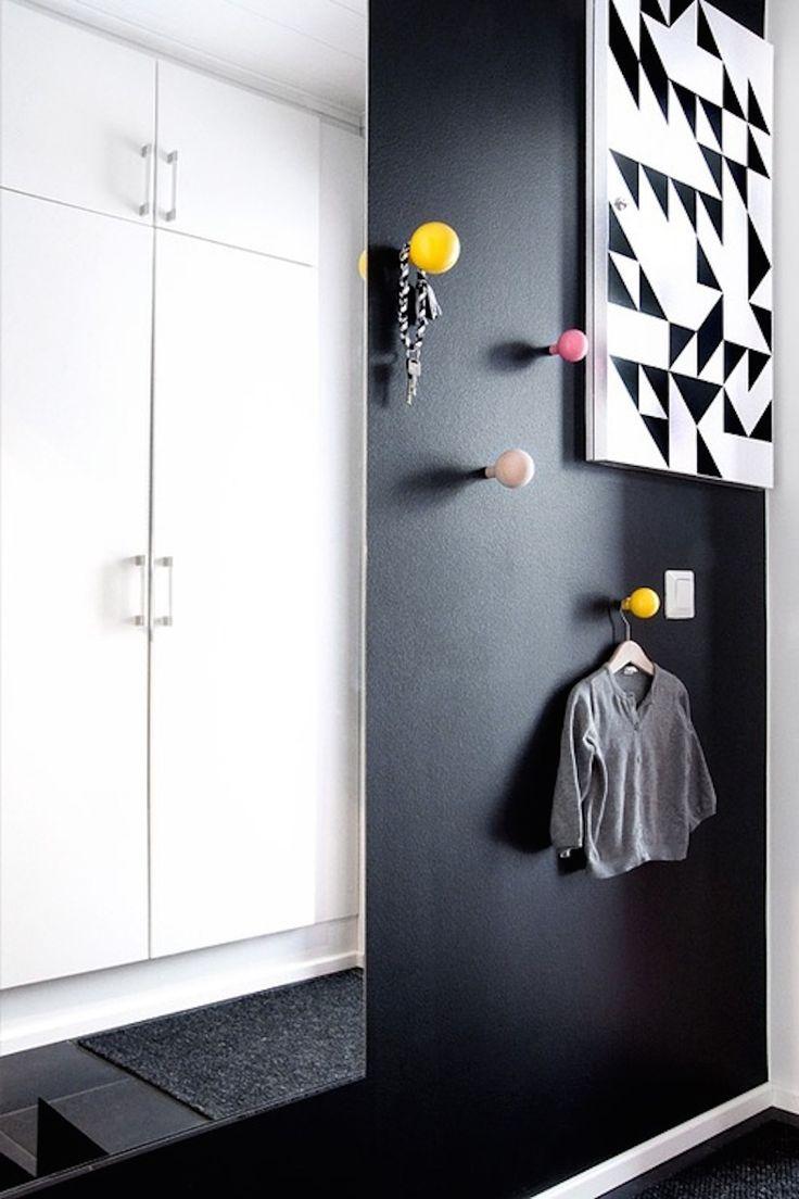 Que tal inovar na decor da sua casa investindo em ganchos diferentes? Esses redondos e coloridos deu o toque especial à essa casa com estilo minimalista preto e branco.