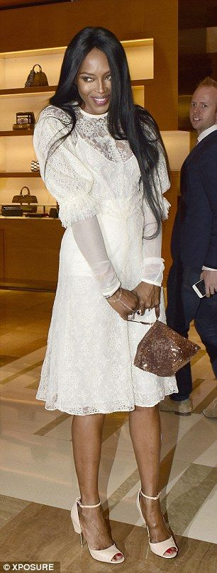A bit of all white: Naomi looked stunning in a white lace dress with a sparkly bag and nud...