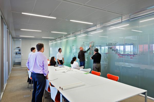 Glass walls in project team rooms provide writing surfaces while also filtering in light to the building's core.