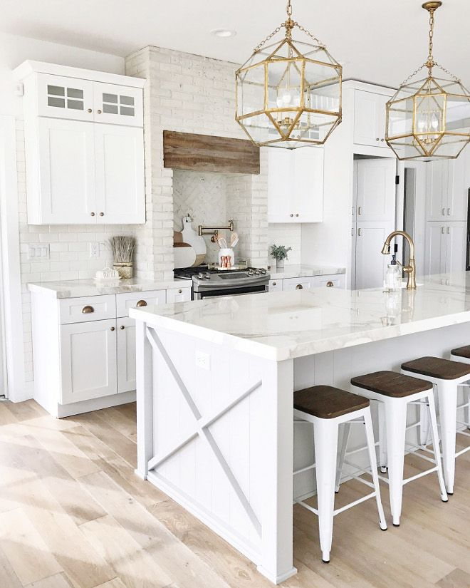 Charmant White Kitchen Design With Natural Wood Floors And Gold Pendant Lights
