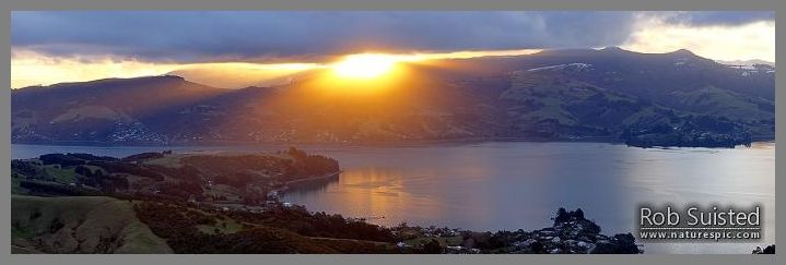 Otago Harbour sunset over Broad Bay, Mount Cargill beyond. Winter panorama.  Otago Peninsula.