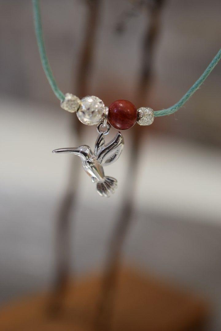KOLIBŘÍK- Náhrdelník vyroben z pevné, hedvábné šňůrky, nastavitelné délky, přetahování přes hlavu, zakončen stříbrnými perlami, medailonkem Impronte ve tvaru stopy. Ozdoben stříbrnými perlami Ag  925/1000, drahým kamenem- Korál a stříbrným komponentem kolibřík.