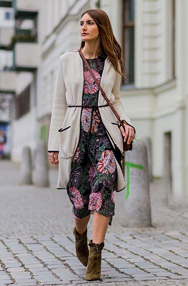 Street style look com vestido colorido floral, cardigan bege e bota marrom.