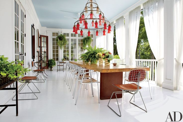 The veranda was added by Spear, who furnished it with an Egyptian chandelier, a dining table by Tucker Robbins, and aluminum armchairs by Knoll.