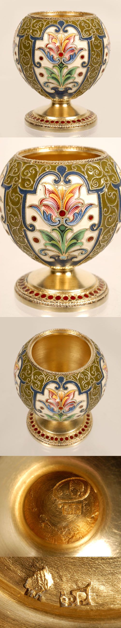 A Russian silver gilt and cloisonne enamel vodka cup, Feodor Ruckert, Moscowq, circa 1896-1908. The bulbous body decorated with multi-color stylized foliate cartouches on a cream ground surrounded by olive green enamel set with scrolling filigree wires.