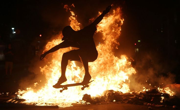 A young man skateboards move in front of a fire set by protesters following a demonstration against proposed federal government reforms in Rio de Janeiro, March 15, 2017. (Mario Tama/Getty Images)