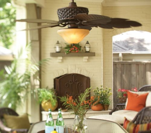 An outdoor ceiling fan with blades shaped like palm leaves.
