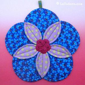 Fabric flower hotpad pattern by La Todera. Easy to make DIY fabric potholder and trivet tutorial. Shown here in Kaffe Fassett fabrics.