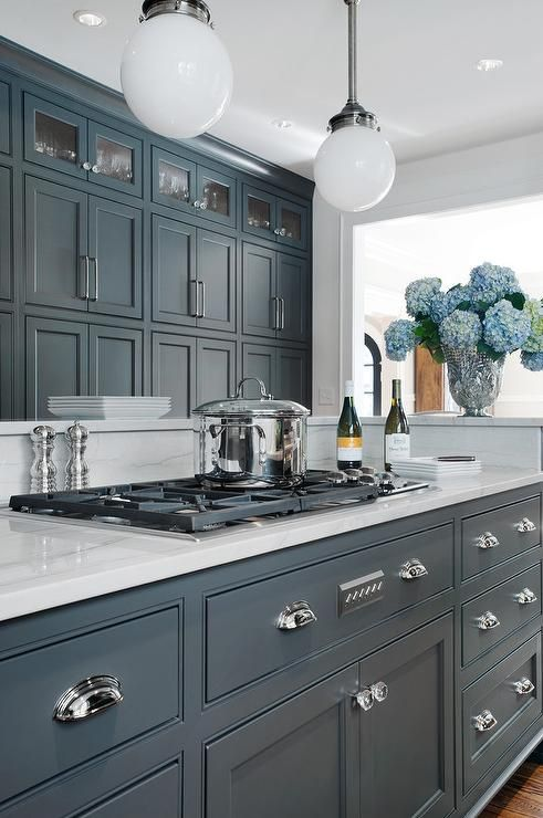 Amazing kitchen features dark gray center island adorned with cup pulls  painted Porter's Paint Gray Bronze paired with