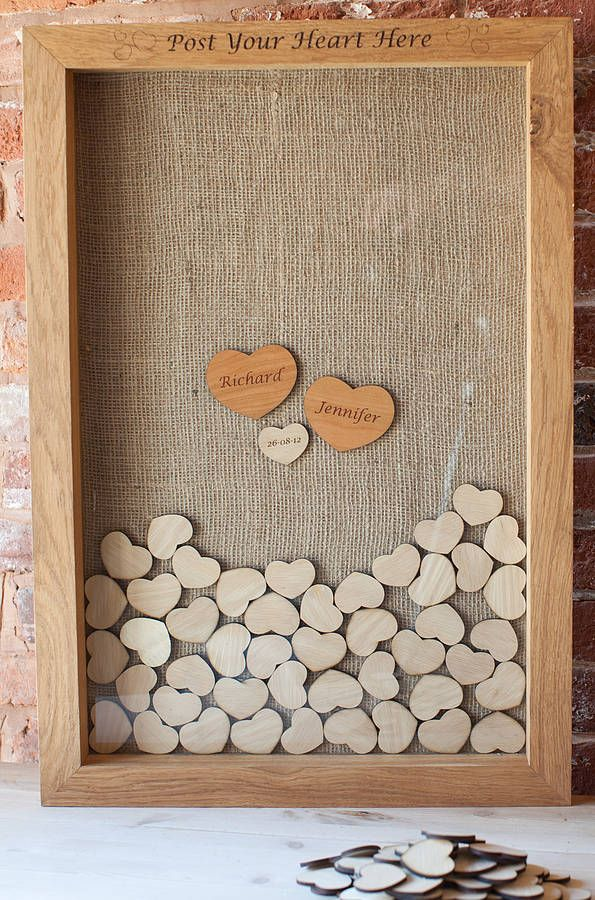 this is super cute shell - this could easily be made - something similar instead of hearts small squares get a arge photo frame with 2x2 on the back bottom and sides then wood behind with a smaller opening in the top to drop in, lined with hessian on the wood behind! personalised drop top guest book by the wedding tree company | notonthehighstreet.com