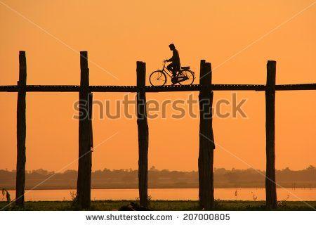 Silhouetted person with a bike on U Bein Bridge at sunset, Amarapura, Mandalay…