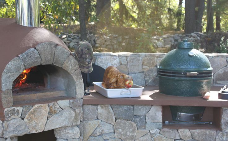 Outdoor Kitchen With A Built In Pizza Oven And Big Green
