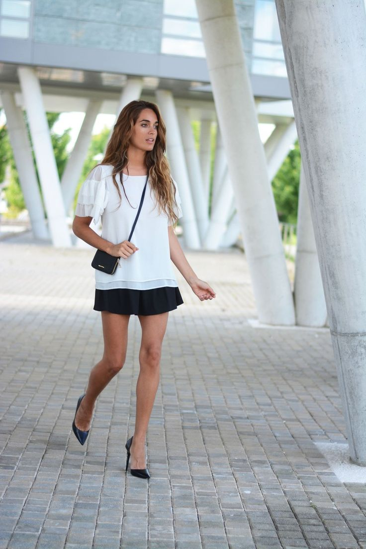 Stella is wearing a white bell sleeve top from Kling, black skirt, mini purse from Mango and black shoes from Zara
