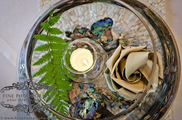 Fish bowl with water, paua pieces, fern and floating candle and flax flower.