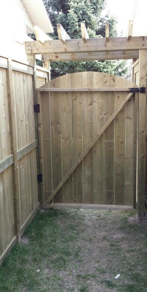 Custom Small pergola over gate with fortress style fence 1 inside yard view