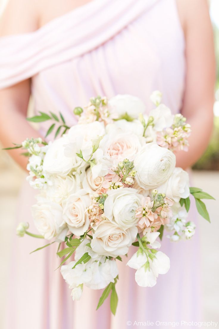 slightly loose bouquet of white o'hara garden rose, white ranunculus, vendela rose, peach stock,white stock & white sweet pea wrapped in cream satin ribbon for bridesmaid in her blush gown.