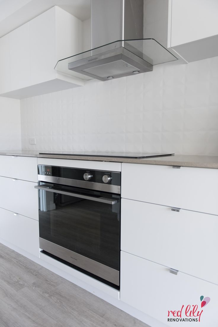Red Lily Renovations - Perth. White Kitchen with Caesarstone benchtop.  Splashback from Ceramo tiles.  Flooring vinyl planks. Fisher and Paykel appliances with induction cooktop.