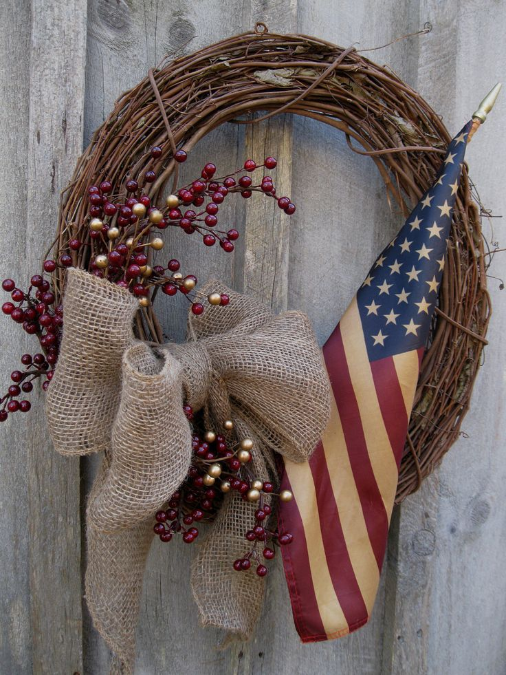 Clusters of Cranberries, a tea-stained American flag & a plush burlap bow on a grapevine wreath.