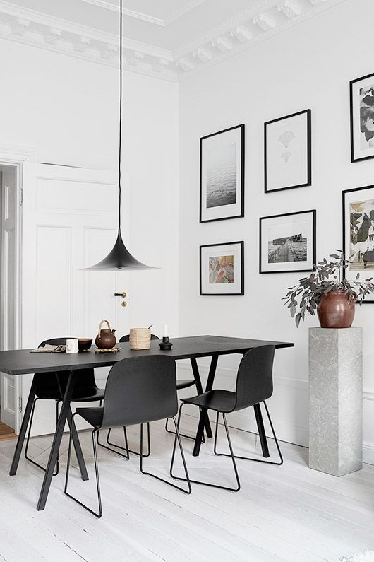 Minimalist dinging area with a black dining table and pendant lamp with art gallery wall.