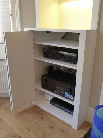 Here A Bifold Cabinet Door Reveals Hidden TV And AV Equipment.